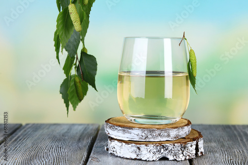 Fotografie, Obraz  Glass of fresh birch sap on a wooden table on nature background