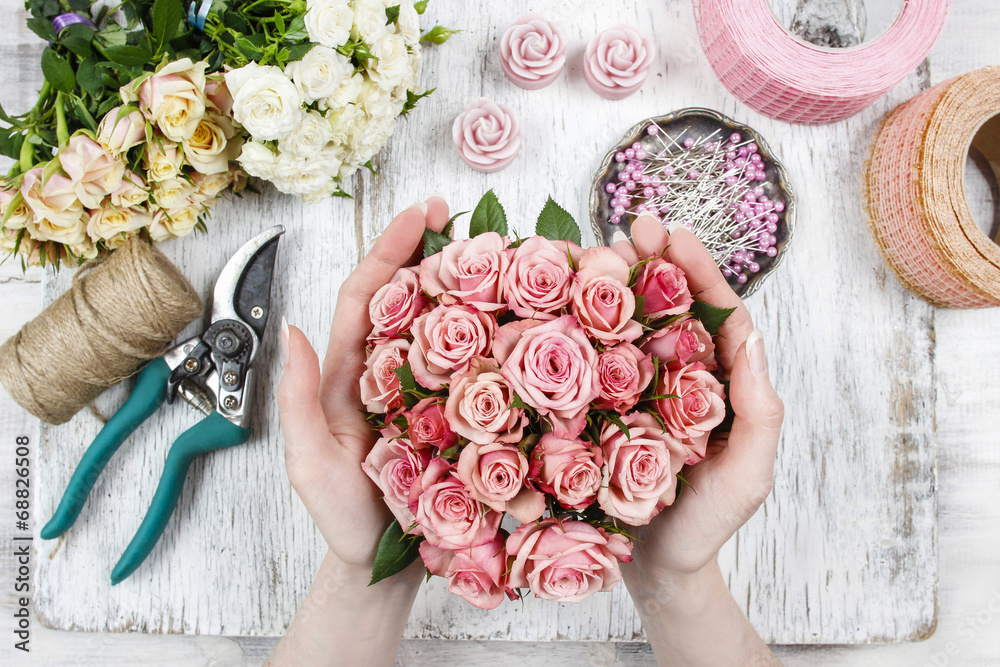 Fototapeta Florist at work. Woman making bouquet of pink roses