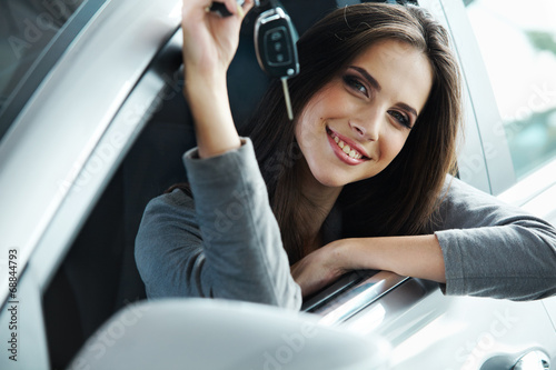 Woman Driver Holding Car Keys siting in Her New Car. Wallpaper Mural