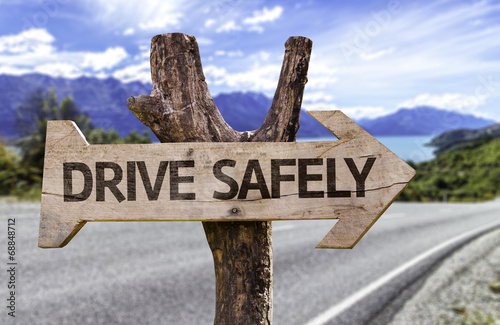 Fotografía  Drive Safely wooden sign with a street background