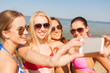 group of smiling women making selfie on beach