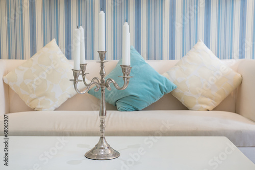 Leinwand Poster candlestick with five  candles on table with sofa in background