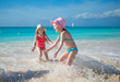 Adorable little girls playing in shallow water at exotic beach