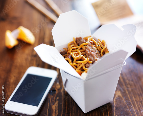 Photo  chinese take out with smart phone on table and menu