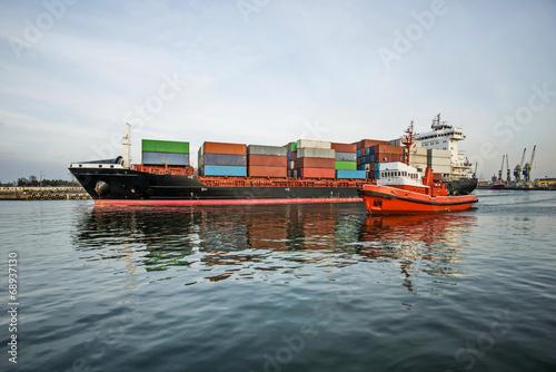 Fotobehang - Kontenerowiec z holownikiem  wypływa z portu