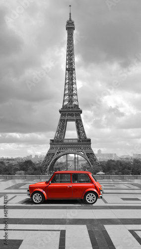 Eiffel tower with car. Black and white photo with red element. #68974310