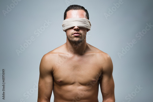 Photo Portrait of young naked blindfold man.