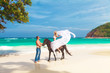 Young couple in love walking with the horse on a tropical beach.