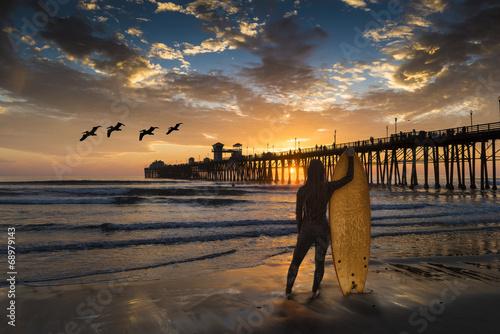 Canvas Print A female surfer admires a sunset near the Oceanside Pier.