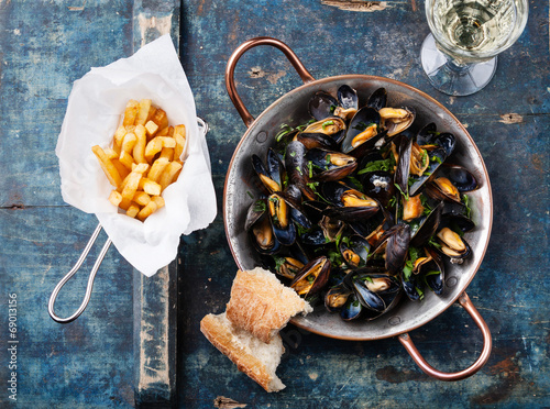 Valokuva  Mussels in copper cooking dish and french fries on blue backgrou