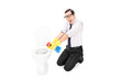 Man cleaning a toilet with disinfecting spray