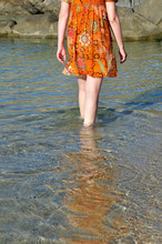 Woman In Colorful Dress Wading Through Sea Water