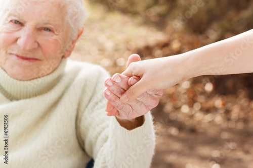 Fotografie, Obraz  Senior woman holding hands with young lady