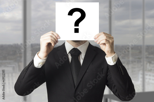 Fotografia  businessman hiding face behind sign question mark