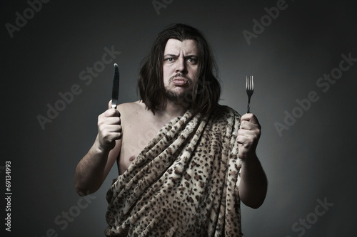 Photo  Hungry wild man wearing leopard skin hold fork and knife.