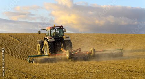 Wiosenne pole,traktor orzący pole pod zasiewy - fototapety na wymiar