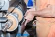 Le cordonnier répare le talon d'une chaussure de femme