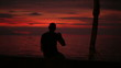 Silhouette of man drinking beer during sunset by the sea