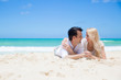 Cheerful couple embracing and lying on the beach on a sunny day