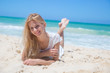 Smiling young girl lying on the sunny beach