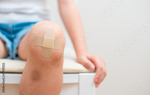 Photo Child knee with an adhesive bandage and bruise.