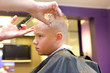 Hairdresser trimming blonde hair of young boy by scissors