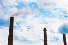 Three Smoke Stacks Of The Industrial Plant Against The Cloudy Sk
