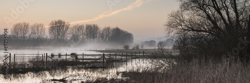 Poster de jardin Gris Panorama landscape of lake in mist with sun glow at sunrise