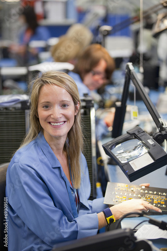 Portrait of smiling technician examining printed circuit board in hi