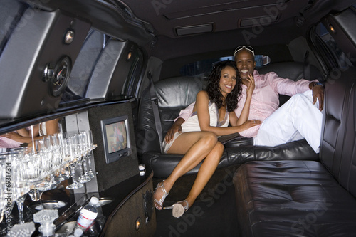 Photographie  Young couple in limousine, smiling, portrait