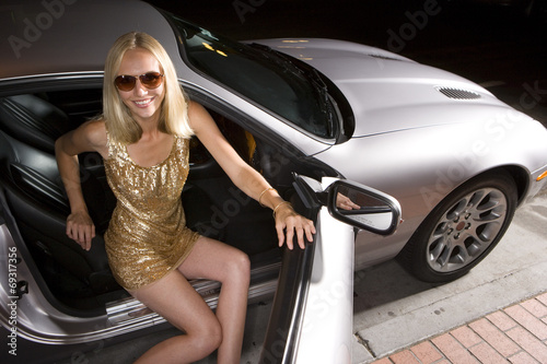 Fotografie, Obraz  Young woman alighting from car at night, elevated view