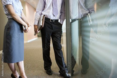 Foto auf AluDibond Bahnhof Businessman and businesswoman talking in corridor beside office window, low section, side view