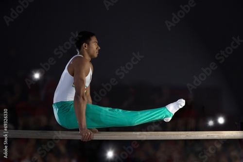 Foto op Canvas Gymnastiek Male gymnast performing on parallel bars, side view