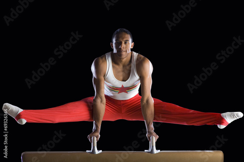 Spoed Foto op Canvas Gymnastiek Male gymnast performing on pommel horse, portrait, low angle view