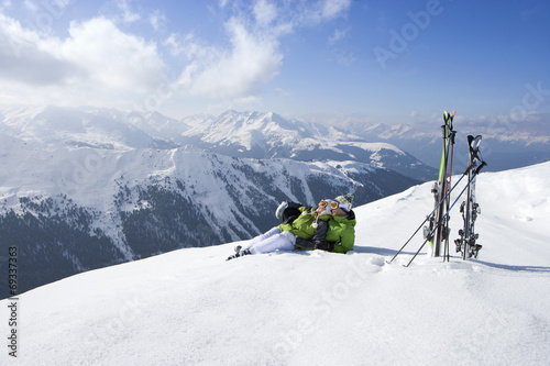 Photo  Couple laying in snow on mountain top with skis