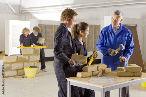 Teacher teaching students bricklaying in vocational school