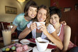 Three young women posing cheek to cheek in cafe, smiling, central woman holding cup of coffee, portrait
