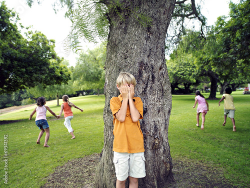 Fotomural  Boy (7-9) with hands covering eyes playing hide and seek in park, hiding from fr