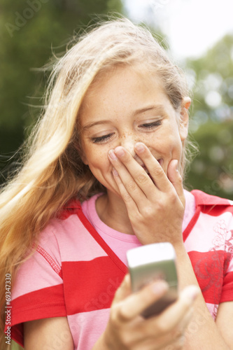Fotografie, Obraz  A teenage girl reading a message on her mobile phone.