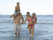 Mid adult couple and their two children in the sea