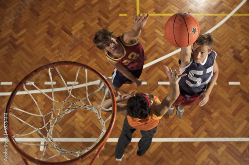 Fotografiet  High angle view of three young men playing basketball