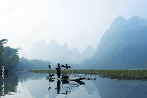 Tuinposter Guilin Cormorant, fish man and Li River scenery sight with fog in sprin