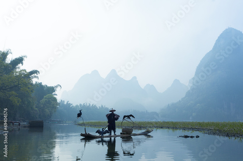 Foto op Canvas Guilin Cormorant, fish man and Li River scenery sight with fog in sprin