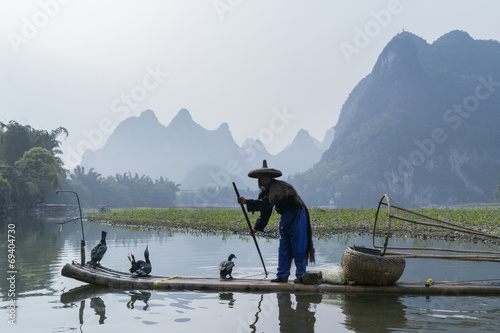 Fotobehang Guilin Cormorant, fish man and Li River scenery sight with fog in sprin