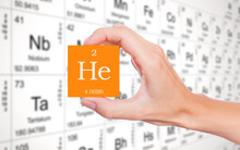 Helium Symbol Handheld In Front Of The Periodic Table
