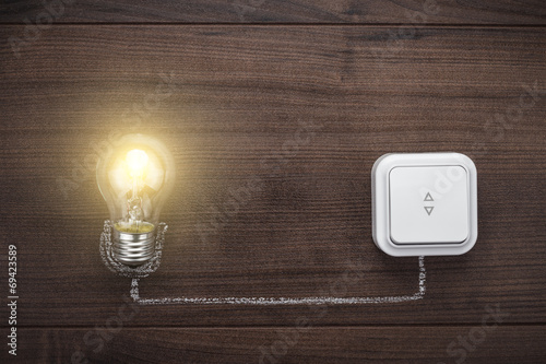 Fotografia glowing bulb uniqueness concept on wooden background