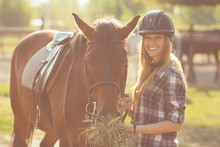 Beautiful Young Woman Feeding Her Horse With Hay