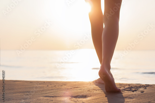 Woman walking on the beach at sunset Canvas Print