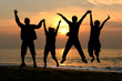 Silhouette Group of happy jumping people man woman at beach