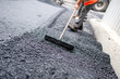 canvas print picture - Worker leveling fresh asphalt on a road building